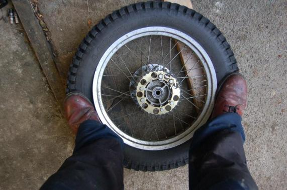 Support the wheel between two blocks of wood thick enough to keep the disc/sprocket off the floor. Remove the valve using a suitable tool, I fit all my bikes with  valve caps which have an integral valve remover, they cost 50p from www.zenoverland.com. Tip; It's easier to break the bead if you weigh 90kg plus and have some shoes with hard soles such as hiking boots. A pair of knackered old Doc's isn't actually the best footwear for this job.