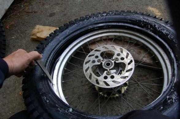 Give the new tyre a liberal coating of soapy water and drop it on top of the rim and tease the tyre over one side. Tip; If you've never done this before it can be like trying to herd a shoal of eels.  Once you've got a section of the tyre over the rim kneel on it whilst you work your way round with the levers. When you're halfway round you can take your knee off.